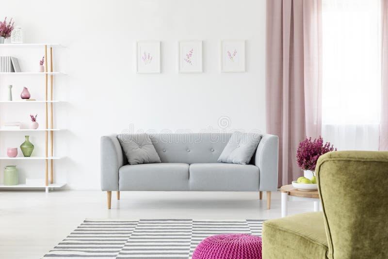 Grauer Aufenthaltsraum mit den Kissen, die in das wirkliche Foto des weißen Wohnzimmers Innen mit Plakaten auf Wand, schmutziges  lizenzfreie stockfotografie