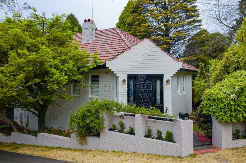 Grauer Backsteinbau mit niedrigem Zaun und belaubtem Garten stockbild