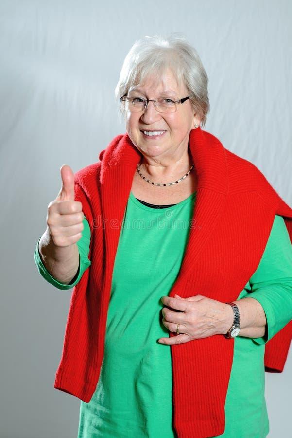 Grauer behaarter weiblicher Senior mit dem Daumen oben lizenzfreie stockfotografie