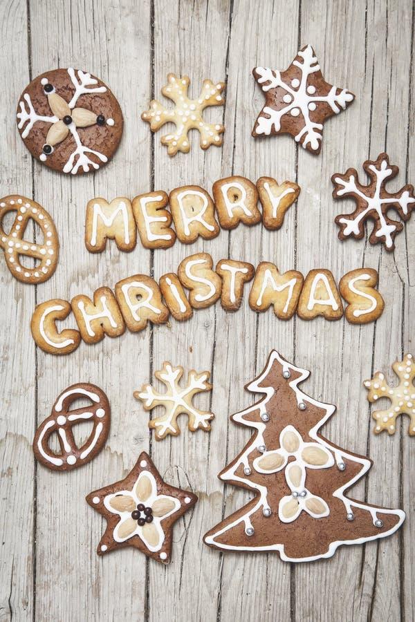 Grauer hölzerner Hintergrund Christmassy mit Lebkuchen und fröhlichem Christma-` s Buchstaben lizenzfreies stockfoto