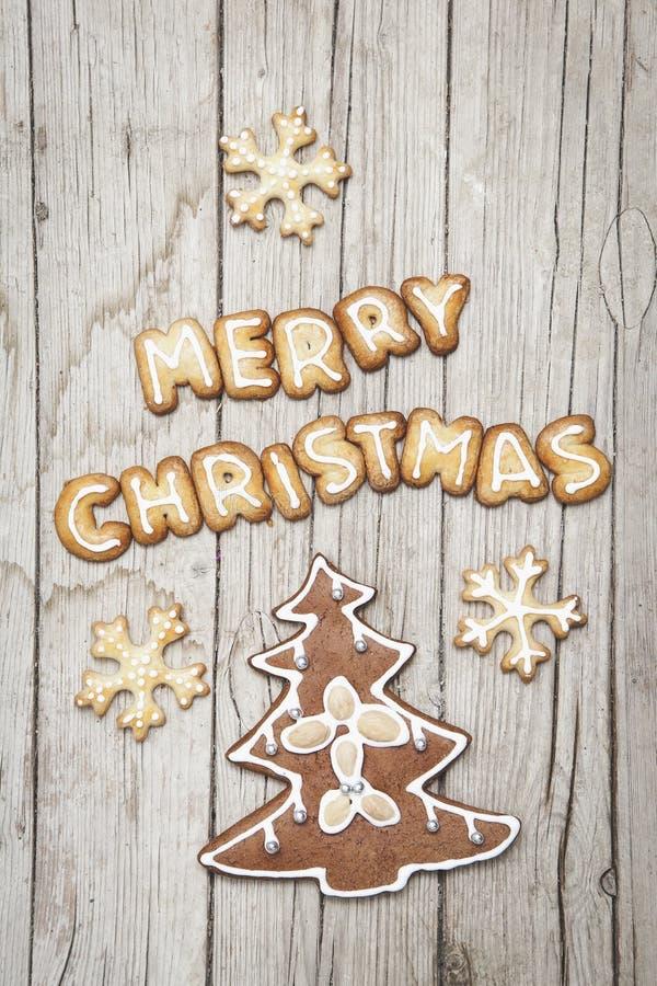 Grauer hölzerner Hintergrund Christmassy mit Lebkuchen und fröhlichem Christma-` s Buchstaben stockfotografie