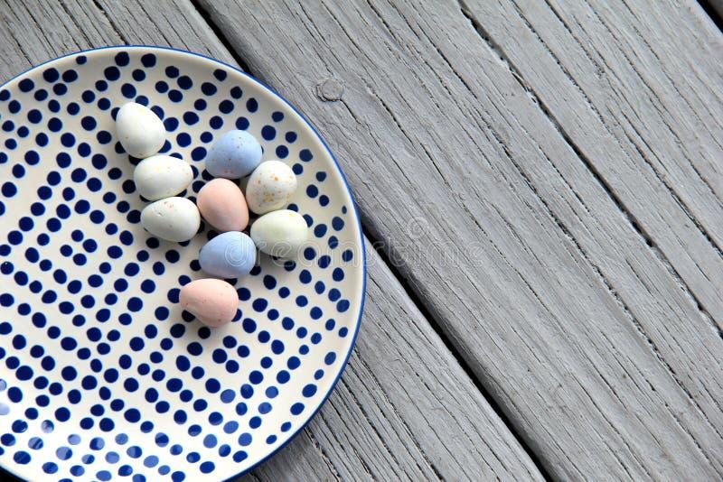 Grauer hölzerner Hintergrund mit der kopierten Platte, die Süßigkeit Ostereier hält stockfoto