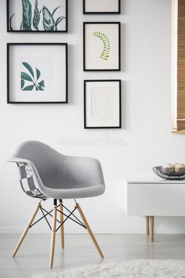 Grauer Lehnsessel nahe bei Schrank im weißen Wohnzimmerinnenraum mit Galerie des Posters Reales Foto stockfotos