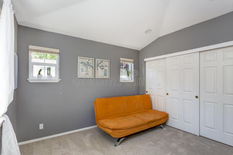 Grauer Rauminnenraum mit Leuchtorangesofa stockbild