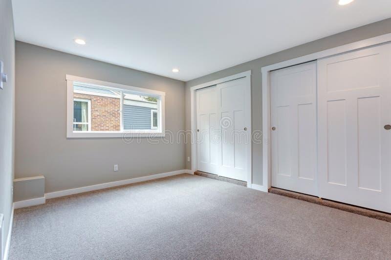 Grauer Schlafzimmerinnenraum mit errichtet im Wandschrank stockfotografie