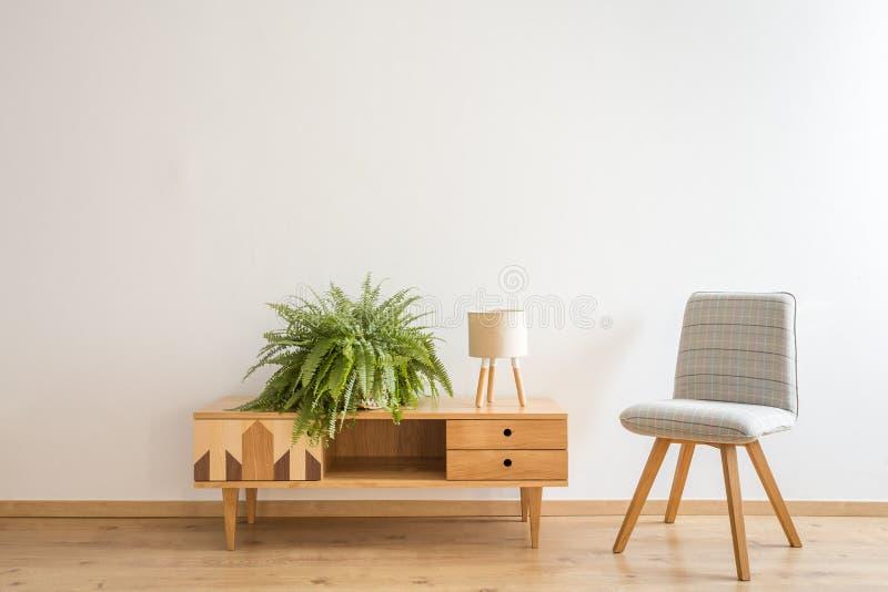 Grauer Stuhl nahe bei Schrank stockbilder