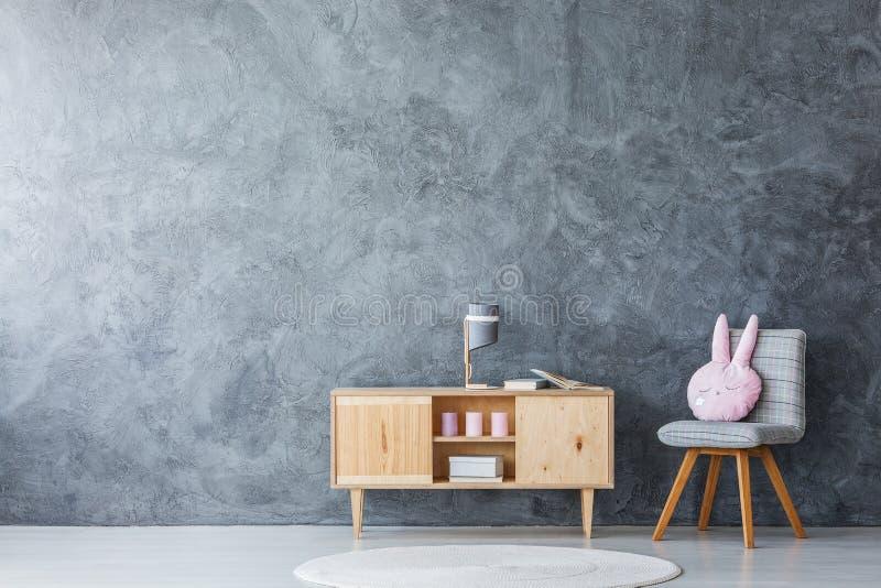 Grauer Stuhl und hölzerner Schrank lizenzfreies stockfoto