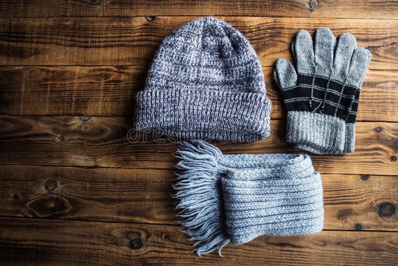 Grauer Winterhut-Handschuhschal auf einem hölzernen bacground stockfotografie