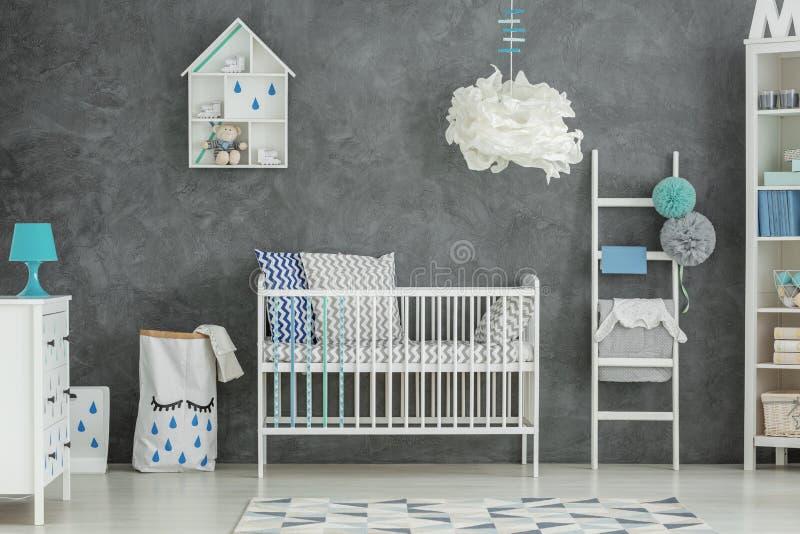 Graues Babyschlafzimmer mit Feldbett lizenzfreies stockfoto
