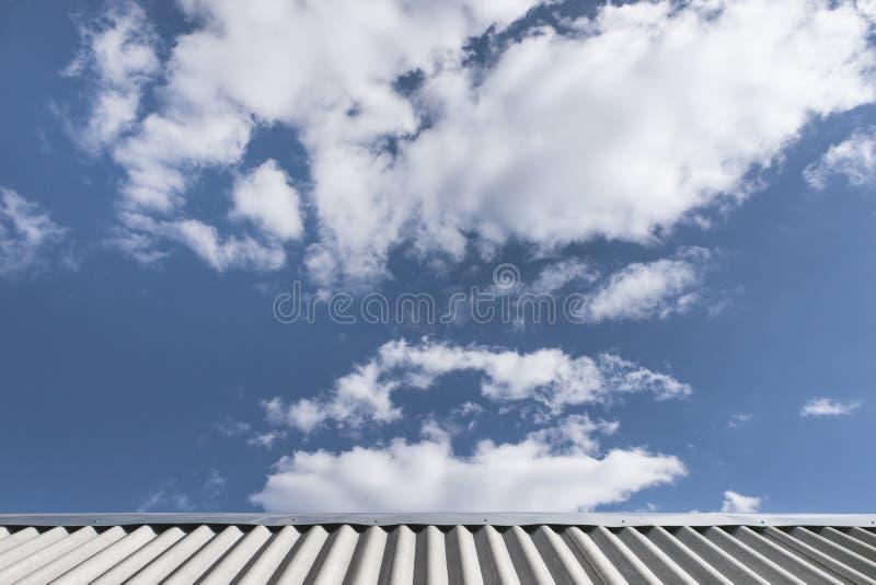 Graues gewelltes Schieferdach und blauer Himmel mit wei?en flaumigen Wolken Sch?nes cloudscape Sonniger Tag Alte Backsteinmauer stockfoto