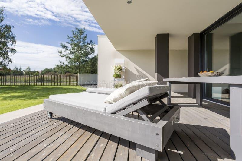 Graues hölzernes deckchair auf Patio lizenzfreie stockfotografie