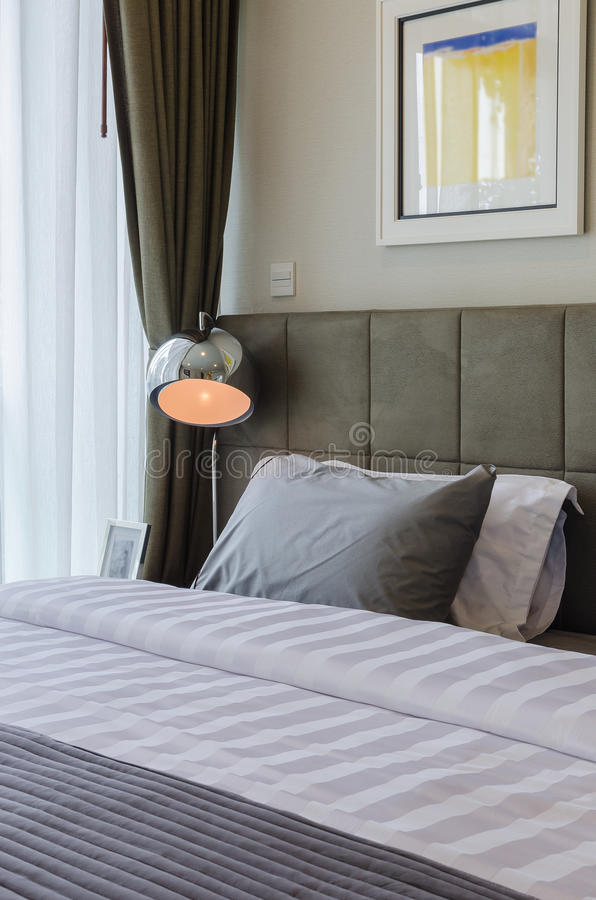 Graues Kissen auf Bett mit moderner Lampe lizenzfreie stockfotos