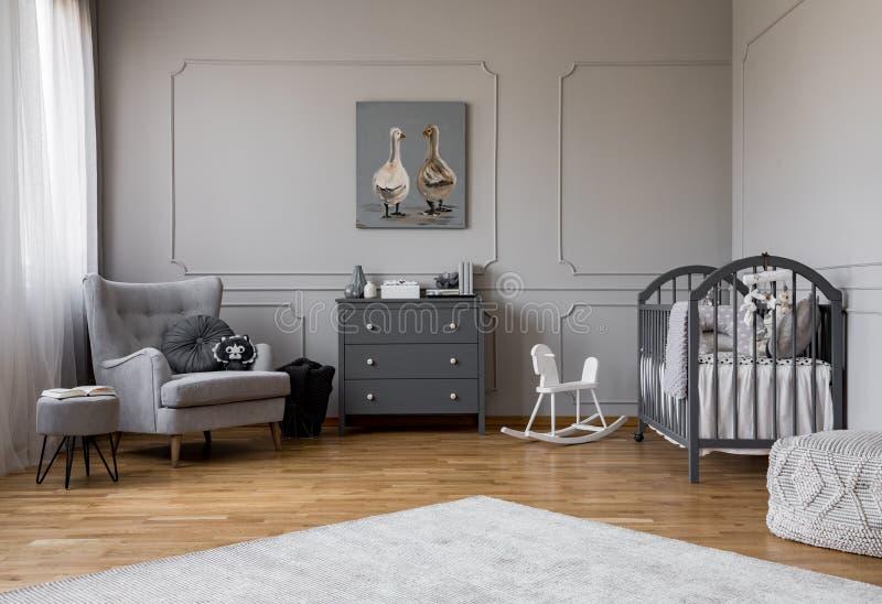 Graues Kommode mitten in elegantem grauem Babyraum mit bequemem Lehnsessel und hölzerner Wiege lizenzfreies stockfoto