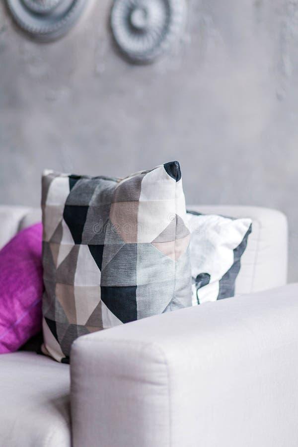 Graues Sofa mit einer Vielzahl von Kissen in einem Raum mit einer grauen Wand lizenzfreie stockfotografie