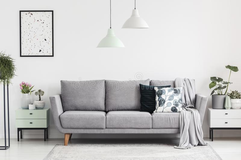 Graues Sofa zwischen Kabinetten mit Anlagen in weißem Wohnzimmer inte stockfotografie