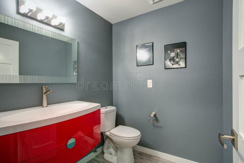 Graues und rotes Badezimmerdesign in frisch nach Hause erneuert stockfotografie