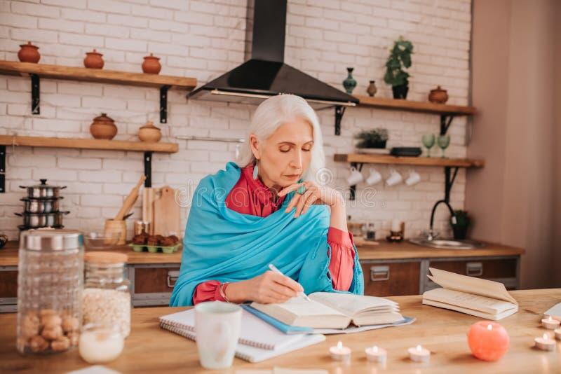 Grauhaarige schöne ältere Dame in blauem Schal, die konzentriert aussieht stockfotografie