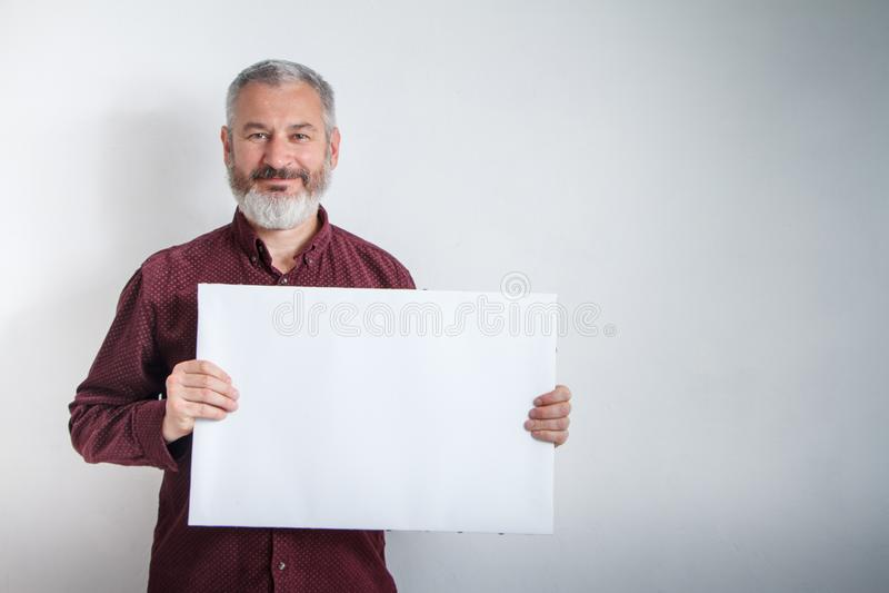 Grauhaariger Mann mit einem Bart, der weißes leeres Schild mit Raum für Text vor ihm hält lizenzfreie stockfotografie