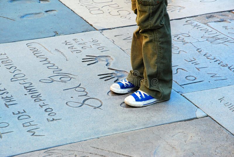 Graumans Chinese Theater. A young person stands in the footprints of Hollywood legends at Grauman`s Chinese Theater in Los Angeles royalty free stock images