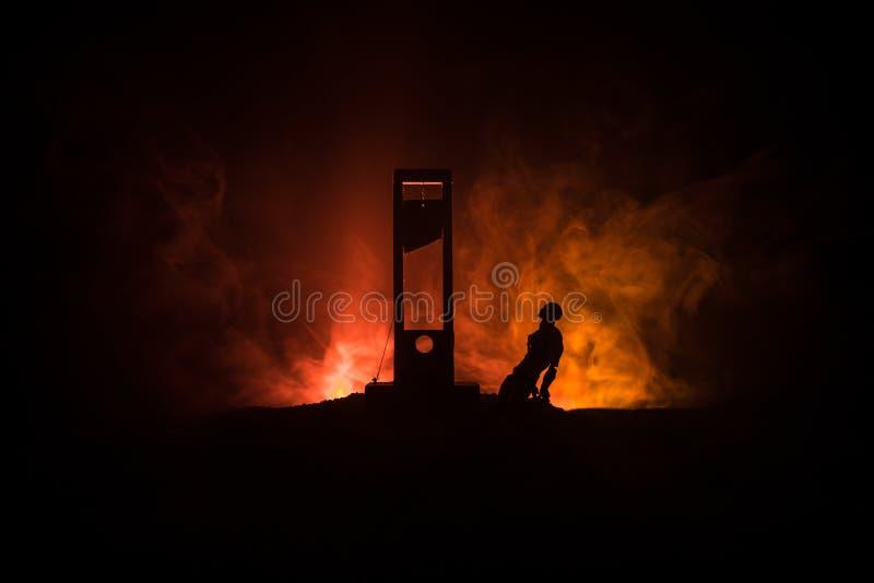 Grausigkeitsansicht der Guillotine Nahaufnahme einer Guillotine auf einem dunklen nebeligen Hintergrund lizenzfreie stockfotos