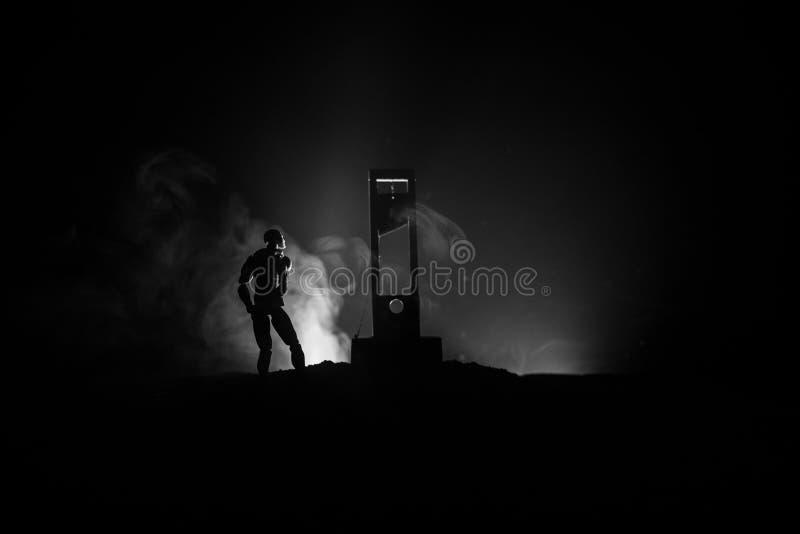Grausigkeitsansicht der Guillotine Nahaufnahme einer Guillotine auf einem dunklen nebeligen Hintergrund stockfotos
