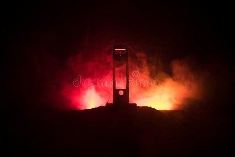Grausigkeitsansicht der Guillotine Nahaufnahme einer Guillotine auf einem dunklen nebeligen Hintergrund stockbilder