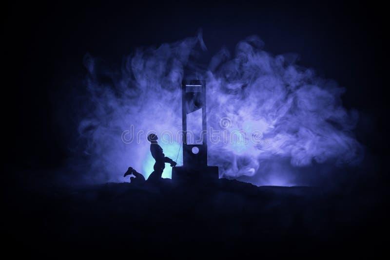 Grausigkeitsansicht der Guillotine Nahaufnahme einer Guillotine auf einem dunklen nebeligen Hintergrund lizenzfreie stockfotografie