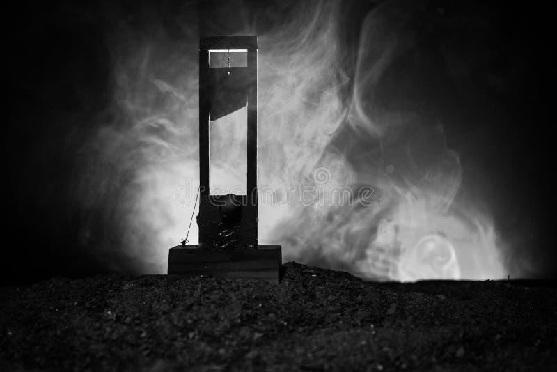Grausigkeitsansicht der Guillotine Nahaufnahme einer Guillotine auf einem dunklen nebeligen Hintergrund stockfotografie