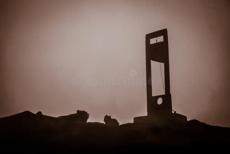 Grausigkeitsansicht der Guillotine Nahaufnahme einer Guillotine auf einem dunklen nebeligen Hintergrund lizenzfreie stockbilder