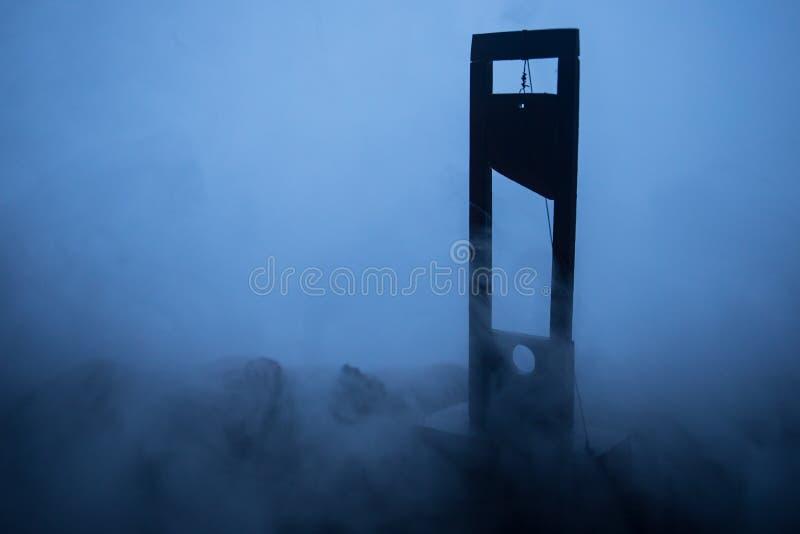 Grausigkeitsansicht der Guillotine Nahaufnahme einer Guillotine auf einem dunklen nebeligen Hintergrund lizenzfreies stockbild