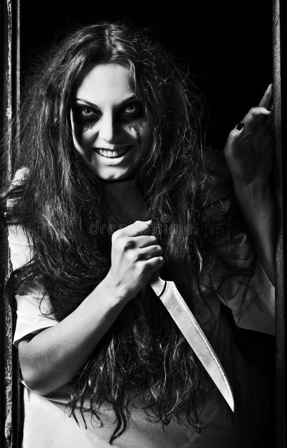 Grausigkeitsart geschossen: verrücktes schlechtes Mädchen mit Messer in den Händen. Schwarzweiss lizenzfreies stockbild