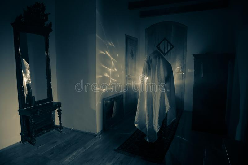 Grausigkeitsschattenbild des Geistes innerhalb der Dunkelkammer mit Spiegel furchtsames ha lizenzfreies stockfoto