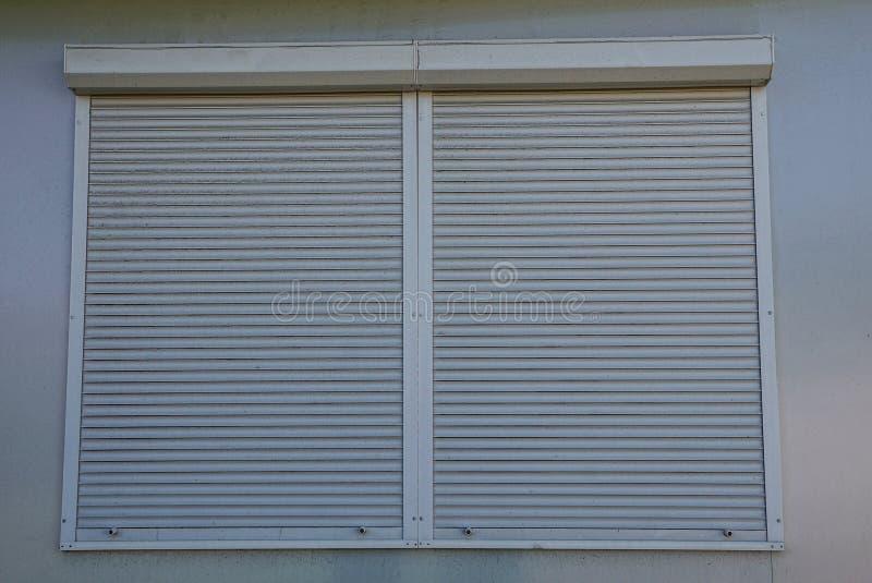 Grauvorhänge auf einem geschlossenen Fenster auf der Wand des Gebäudes lizenzfreie stockbilder