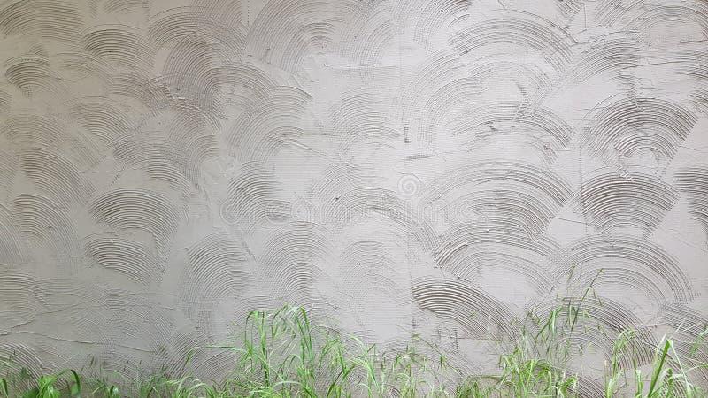 Grauzementwand, die mit geometrischem Wellenmuster des Kreises vergipst stockbild