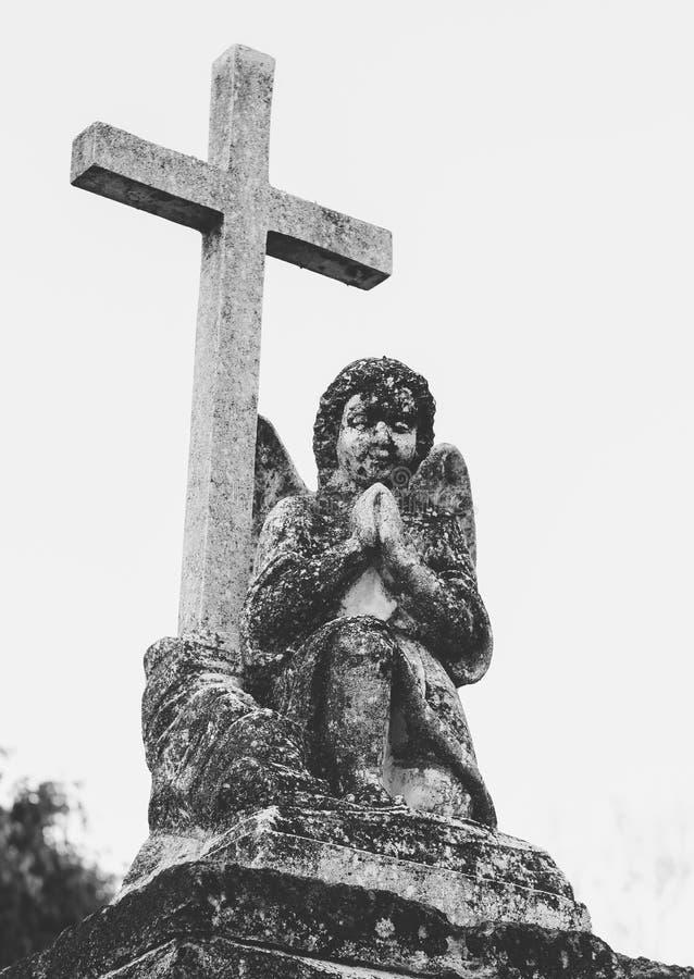 Grav av ett barn med en kerub och ett kors som göras med marmor royaltyfri fotografi