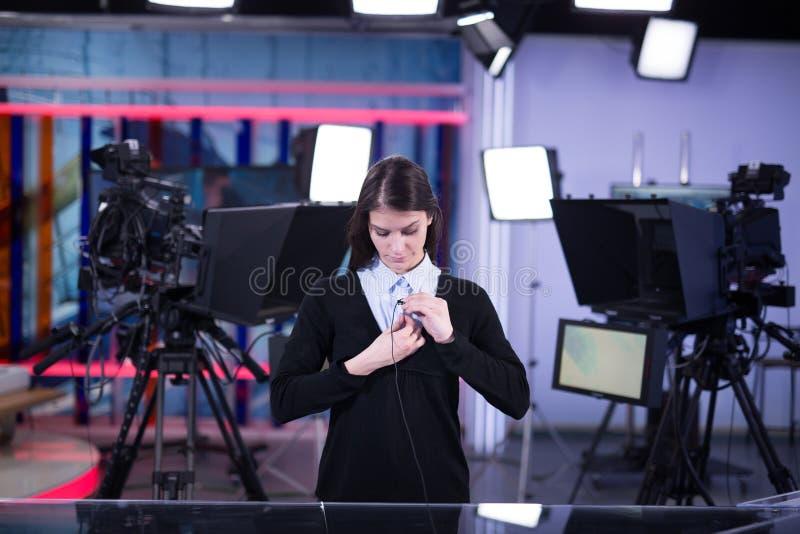 Gravação do apresentador da televisão no estúdio da notícia Âncora fêmea do journalista que apresenta o relatório comercial, grav imagem de stock