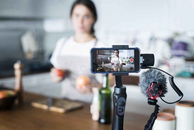 Gravação fêmea do blogger que cozinha a transmissão relativa em casa fotos de stock