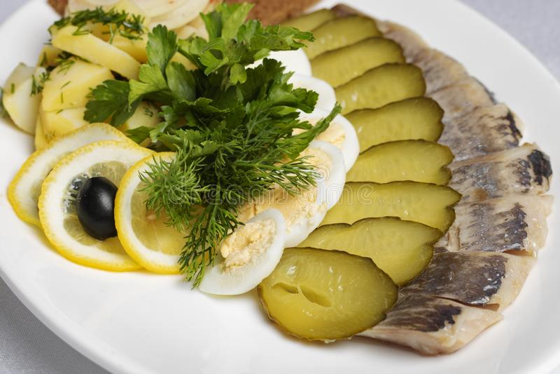 Gravade gurkor, potatis och ägg med oliv och citronen, kallt mål royaltyfri bild