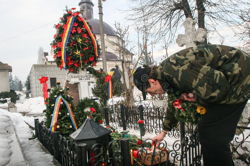 The grave of communist dictator Nicolae Ceausescu. Bucharest, Romania, December 25, 2009: A man lights a candle at the grave of Romania`s late communist dictator stock images