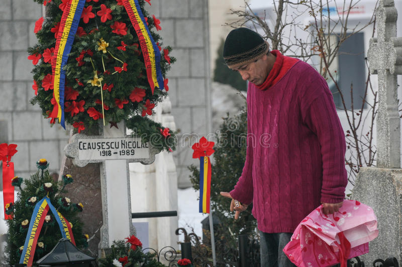 The grave of communist dictator Nicolae Ceausescu. Bucharest, Romania, December 25, 2009: A poor man is praying at the grave of Romania`s late communist dictator royalty free stock images