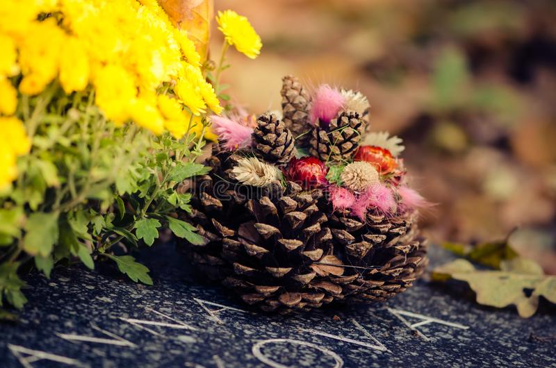 Grave covered by autumnal leaves and pine cone stock photos