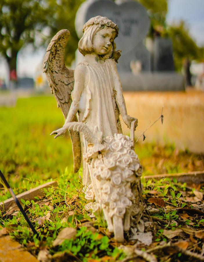 A grave decoration or grave statue. A Angelic winged girl grave statue with a wheelbarrow full of flowers. The statue is made out of alabaster stock image