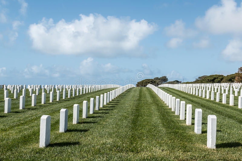 Grave Markers at Fort Rosecrans National Cemetery in San Diego. Grave markers in rows with a cloudy blue sky at Fort Rosecrans National Cemetery in San Diego stock photos