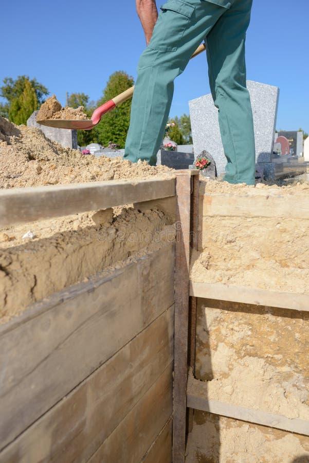 Gravedigger głębienie w cmentarzu zdjęcie stock