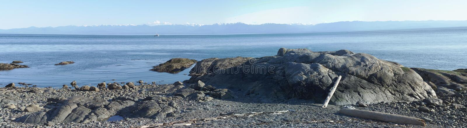Gravel beach with spectacular panoramic view of mountain range. Gravel beach with spectacular panoramic view of the Washington State's Olympic Mountain royalty free stock photos