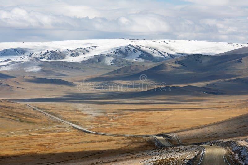 Deserted gravel road across Mongolia steppe towards Gobi. Gravel road across Mongolia steppe, off-road adventure. Autumn 2018 royalty free stock image