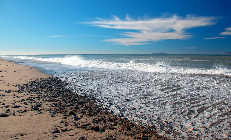 Gravel and Seafoam waves on beach at McGrath State Park in Ventura - Oxnard California USA. Gravel and Seafoam waves on beach at McGrath State Park in Ventura royalty free stock image