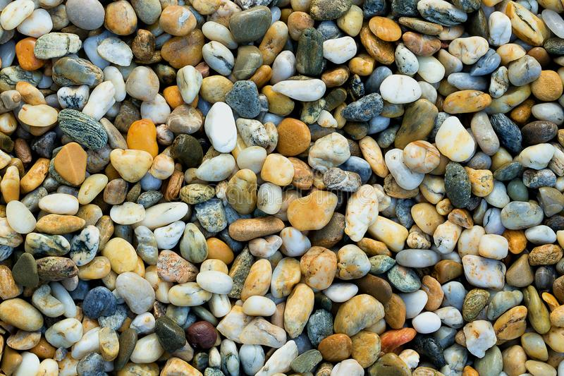 Gravel texture. Small stones, little rocks, pebbles in many shades of grey, white, brown, blue, yellow colour. Background of small stock photography