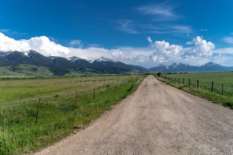 Gravelez le chemin de terre avec des lignes électriques menant dans les montagnes d'Absaroka du Montana images libres de droits