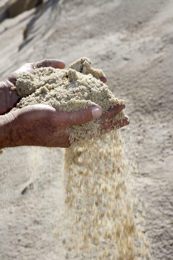 Gravelez le sable dans des mains de l'homme à l'arrière-plan de carrière image stock